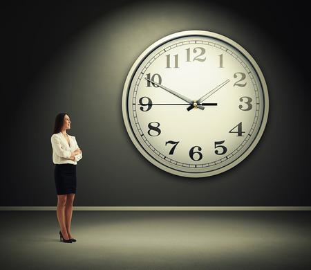 reloj: sonriente de negocios de pie en una habitación oscura con gran reloj en la pared Foto de archivo