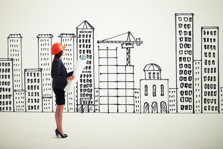 sideview: sideview of businesswoman in orange hardhat with blueprint looking at drawing houses Stock Photo