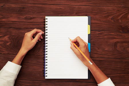 top view of womans hands with empty notebook on wooden table