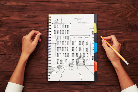 lapiz: vista superior de casas dibujadas a mano en una libreta y un lápiz en la mano de la mujer Foto de archivo