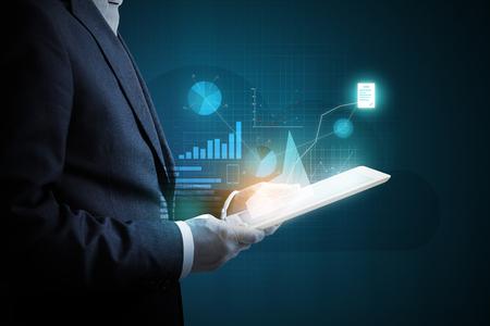man met een tablet pc analyseren virtuele schema van financiële activiteiten over donkere achtergrond