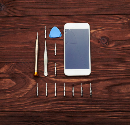 bekijken van boven op smartphone met gebroken scherm en hulpmiddelen over houten tafel Stockfoto