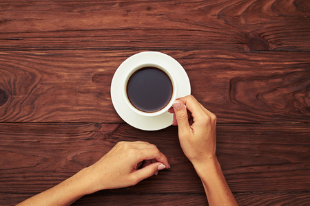 top view of womans hands holding cup of black coffee over brown wooden table
