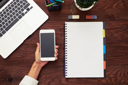 tabla de surf: Vista desde arriba de la hembra teléfono inteligente explotación de la mano sobre la mesa de madera con ordenador portátil y cuaderno vacío