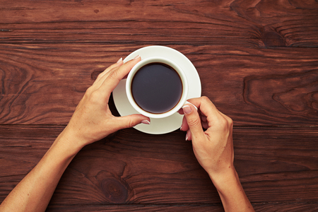 tea table: view from above on womans hands holding cup of coffee over wooden table Stock Photo