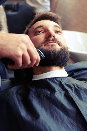 electric razor: barber shaving beard with electric razor of handsome client in professional barbershop