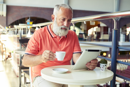 middleaged: middle-aged serious man drinking coffee and looking at tablet pc in cafe