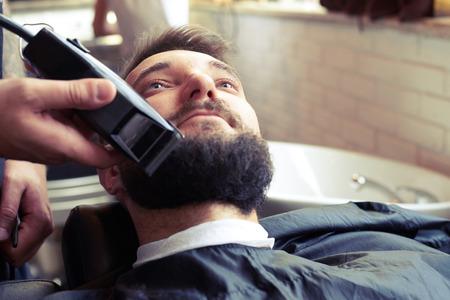 electric razor: barber shaving beard with electric razor in vintage barber shop