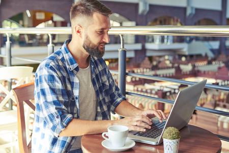 man with laptop: young man having coffee break and using laptop in cafe