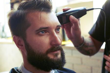peluquero: barbero corte de pelo con maquinilla el�ctrica en una peluquer�a Foto de archivo