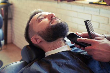 electric razor: barber shaving beard with electric razor and holding comb in barbershop