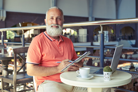 senior men: cheerful senior man holding pencil with notepad and looking at camera in cafe