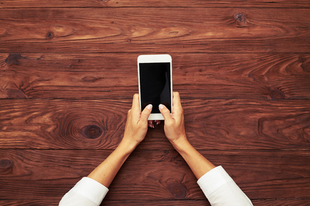 handphone: view from above on womans hands typing on smartphone over wooden brown table Stock Photo