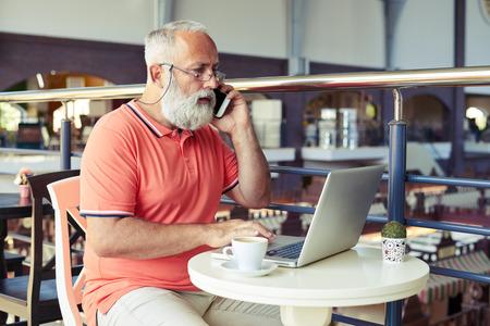 cafe internet: hombre mayor hablando por tel�fono y mirando port�til en el caf�
