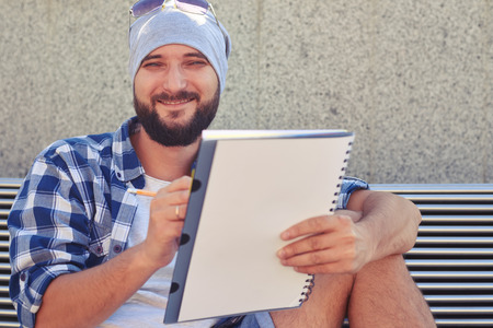young adult man: portrait of stylish young adult man with white notepad