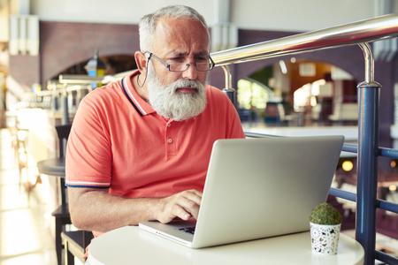 usando computadora: hombre mayor serio trabajo con ordenador portátil en el café