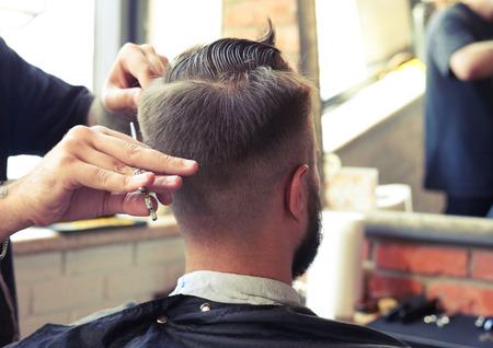 peluquero: vista posterior del hombre en peluquer�a. barbero pelo de corte con tijeras