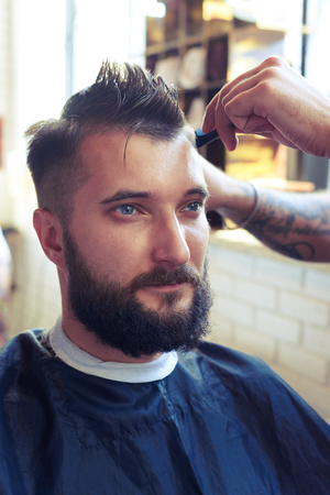 barber: portrait of handsome man with beard in barber shop. barber cutting hair with scissors and comb Stock Photo