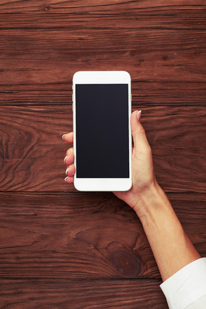 view from above on womans hand with smartphone over wooden background Standard-Bild