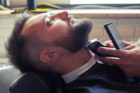 electric razor: sideview portrait of handsome man in professional barbershop. barber shaving beard with electric razor Stock Photo