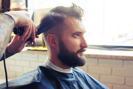 peluquero: pelo corte peluquero con maquinilla el�ctrica y peine en una peluquer�a Foto de archivo