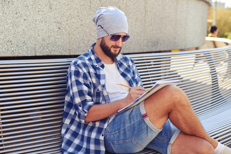 young adult man: stylish young adult man sitting on bench and writing in notebook at outdoors Stock Photo