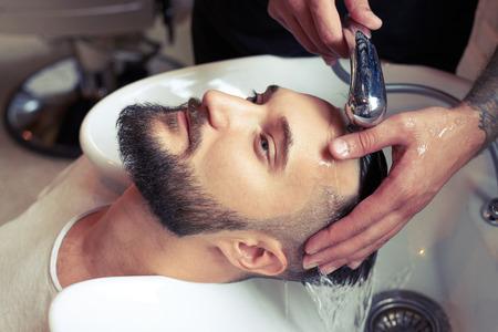 barbero: barbero hombre cabeza de lavado en la barbería Foto de archivo
