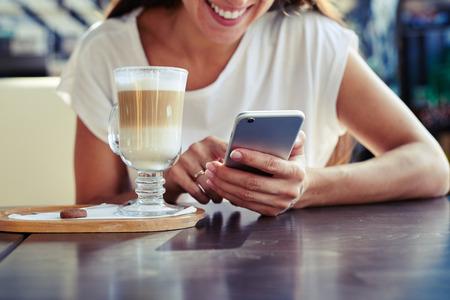 Ritratto di giovane donna attraente usando il suo smartphone in caffè Archivio Fotografico - 46201435