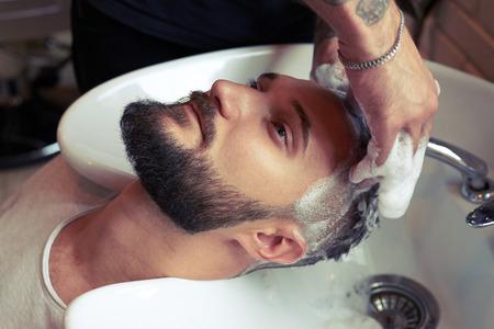 barber washing man head in stylish barbershop