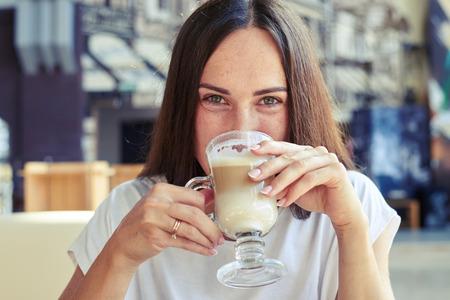 capuchino: mujer alegre beber capuchino y mirando a la cámara en el café