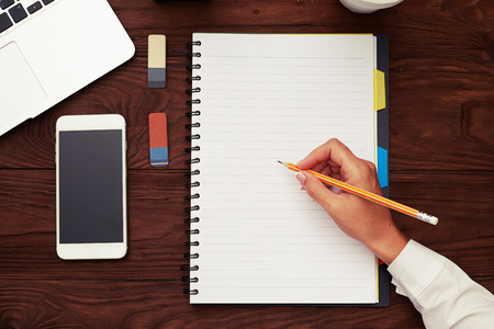 write: top view of womans hand holding pencil and ready to writing on empty white notepad over wooden table