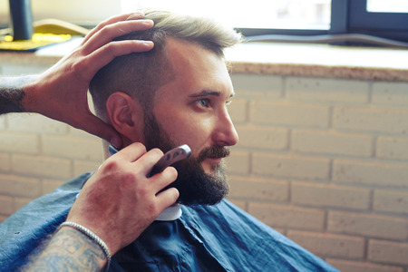 barber: portrait of handsome man in barbershop. barber shaving man with straight razor Stock Photo