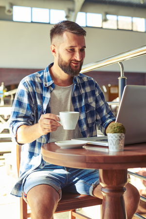 young adult man: cheerful young adult man drinking coffee and using laptop in cafe