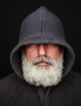 black head and moustache: bearded senior man under the hood over black background