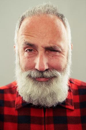 bigote: hombre sonriente senior con barba gris de pelo mirando a la cámara y guiñando un ojo sobre fondo gris claro Foto de archivo