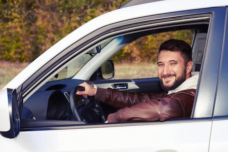 chofer: hombre feliz que conduce su coche y mirando a la cámara