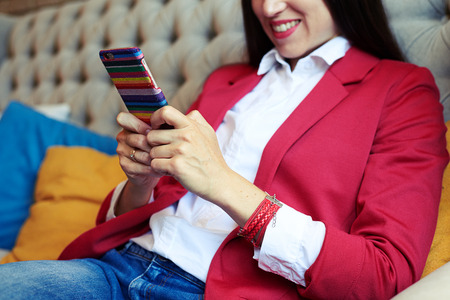 mobile sms: smiley young woman sitting on sofa and chatting on smartphone
