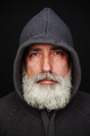 cowl: portrait of bearded senior man in the hood over black background