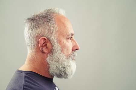 profile face: sideview of senior bearded man over light grey background with empty copyspace