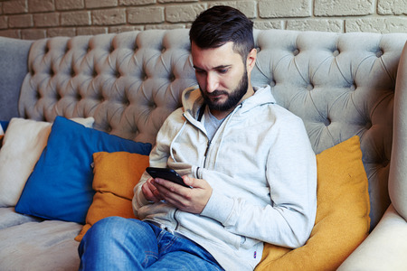 young adult man: handsome young adult man sitting on sofa and using his smartphone