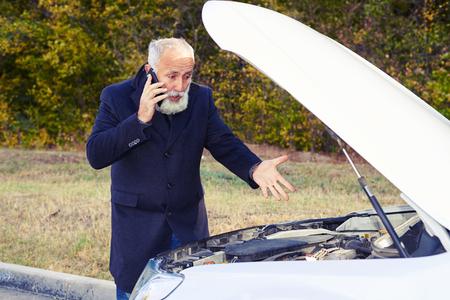 hombre viejo: hombre mayor descontento hablando por teléfono y mirando bajo el capó del coche de la ruptura Foto de archivo