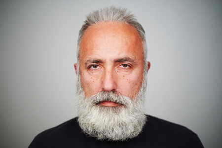 middleaged: close-up portrait of middle-aged man with grey-haired beard over grey background