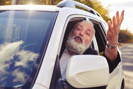 personas enojadas: hombre descontento gritando desde la ventana de su coche