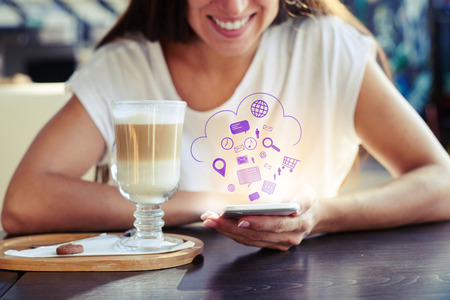 portrait of smiley young woman sitting in cafe and using her smartphone. virtual icons floating in the air