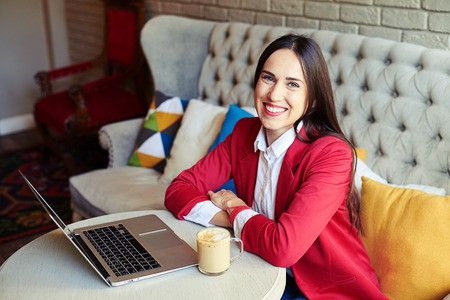 woman resting: successful young businesswoman with laptop in cafe