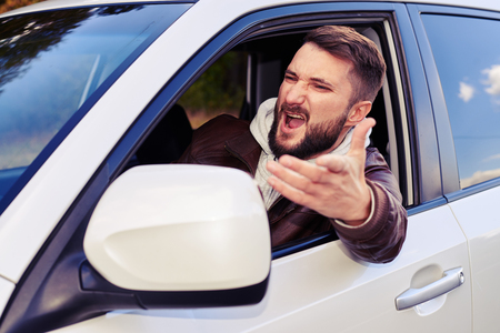 discontented: discontented young man shouting from the window of his car Stock Photo