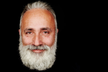 volto uomo: close-up ritratto di smiley uomo barbuto su sfondo nero con copyspace vuoto