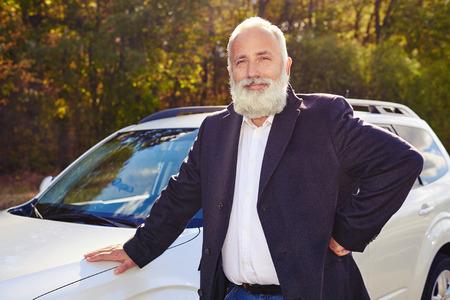 smiling businessman: portrait of smiley senior man near his white car at outdoor