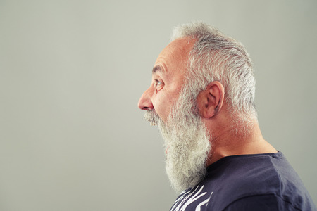 male face profile: sideview portrait of screaming senior man with grey-haired beard Stock Photo