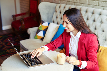 Caucasian woman: cheerful young woman working with laptop in cafe Stock Photo